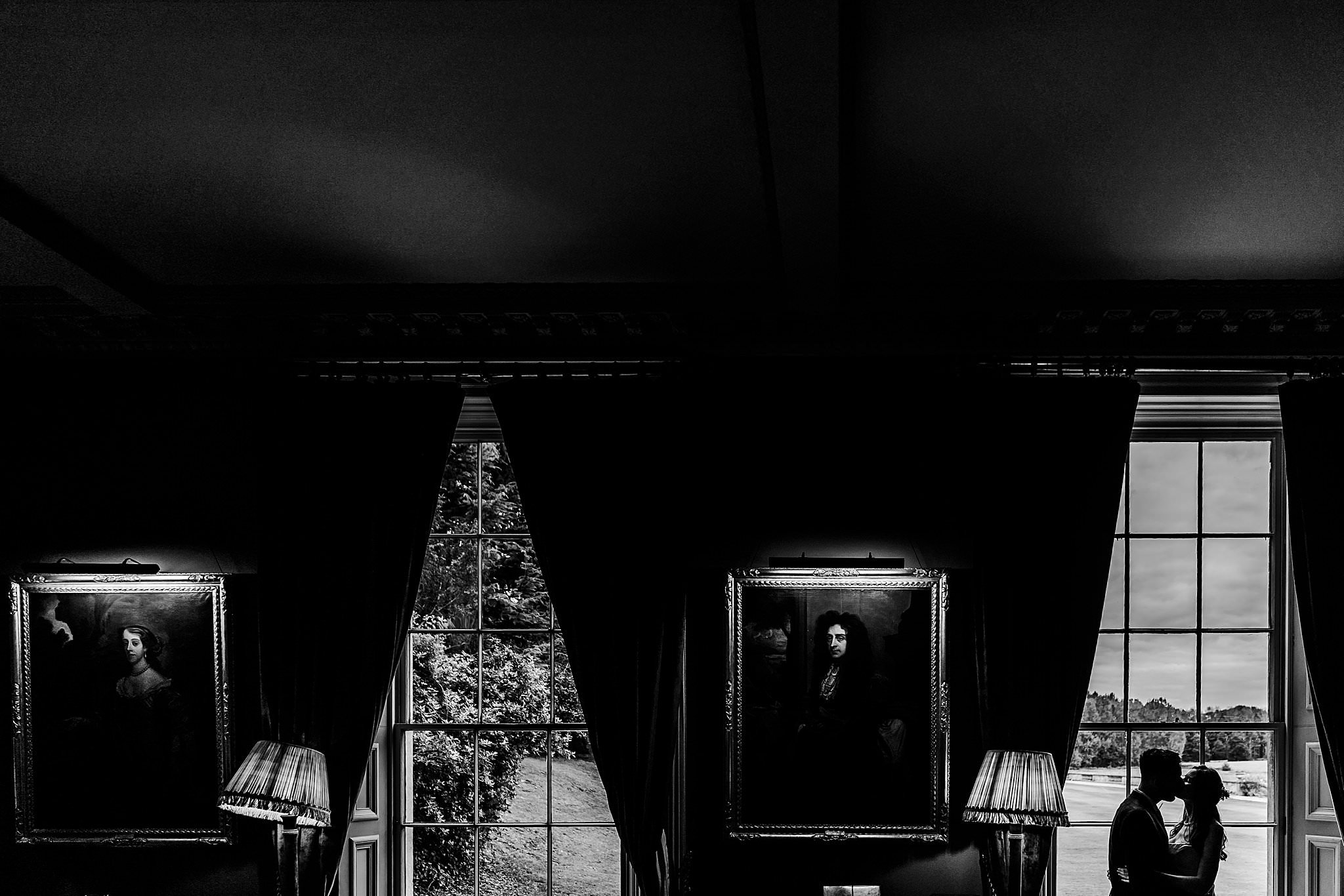 Black and white silhouette of bride and groom framed in the windows of Prestwold Hall with paintings lit up
