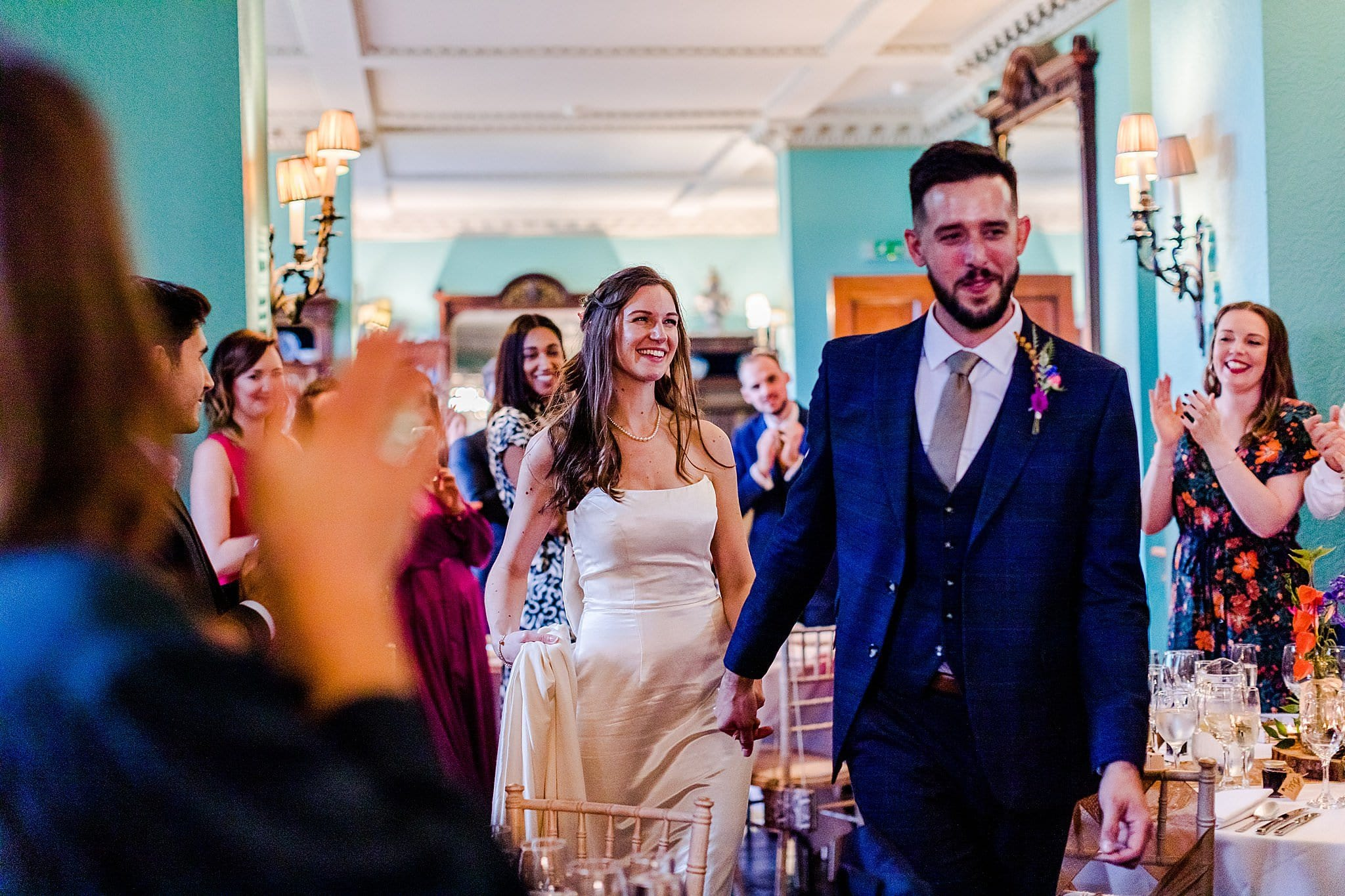 Bride and groom enter the room to great applause from their smiling guests at Prestwold Hall