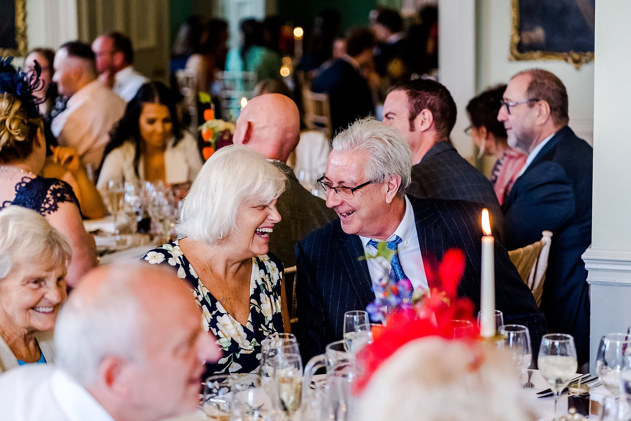 Wedding guests enjoying a joke together whilst waiting for food at Prestwold Hall
