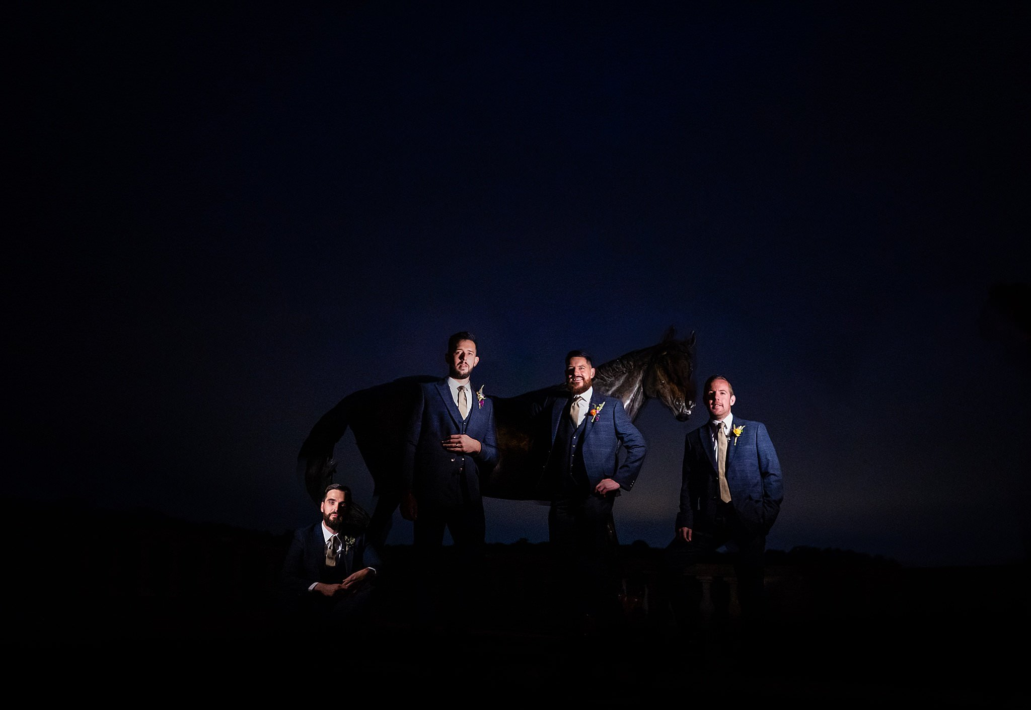 Groom and his groomsmen pose in front of Prestwold Hall Horse Statue whilst being dramatically lit