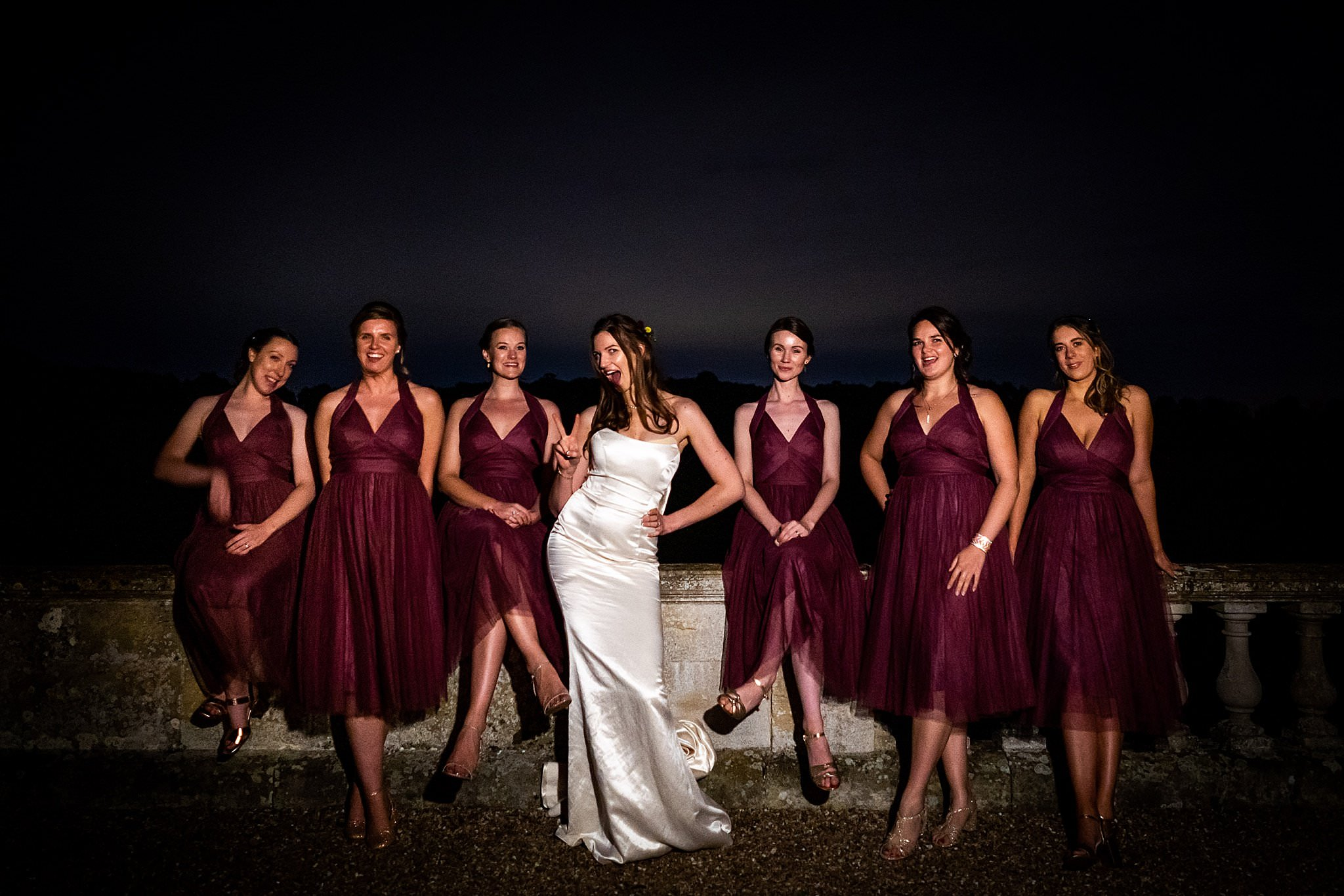 Bride poses with her bridesmaids outside at night at Prestwold Hall