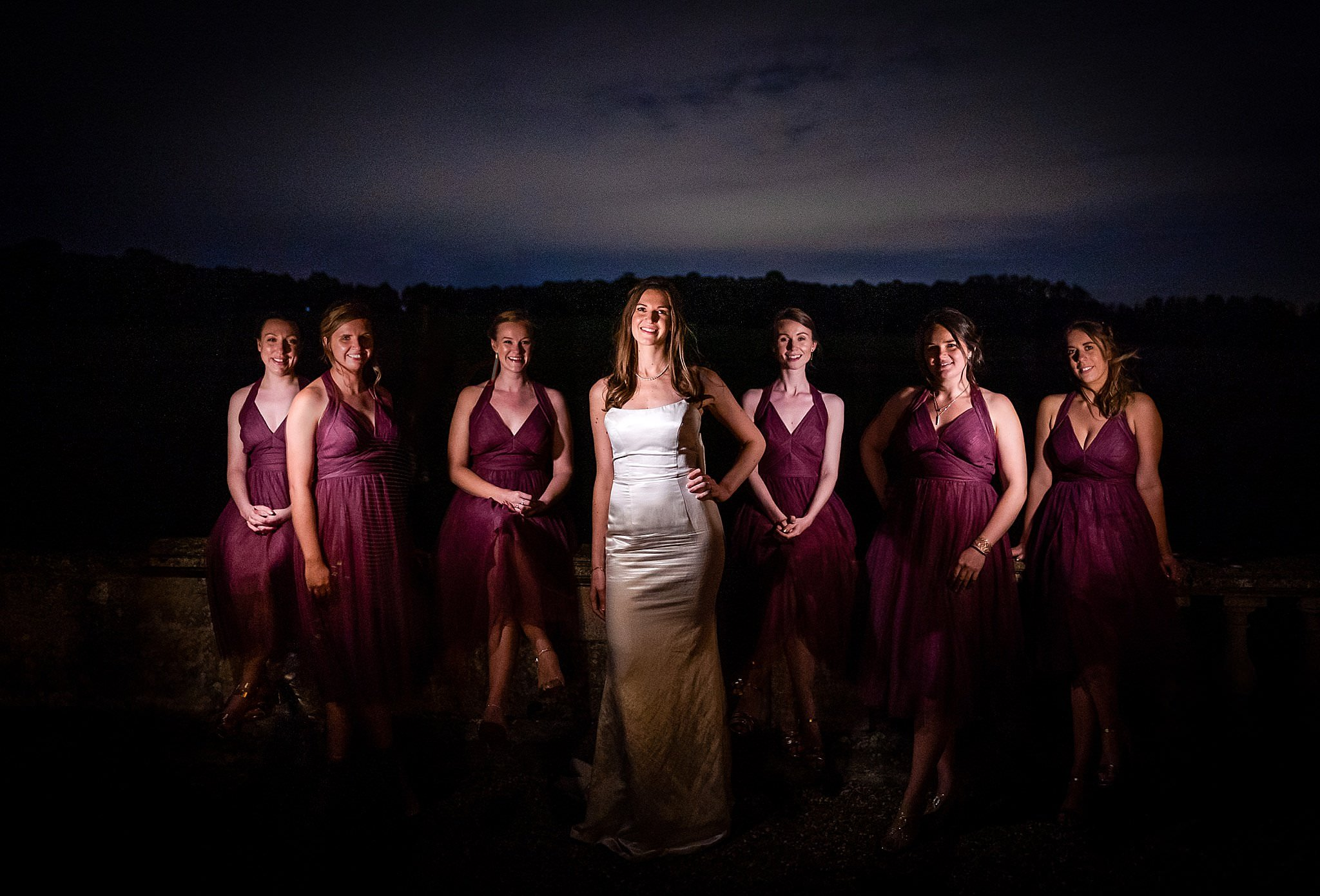Bride posing with her bridesmaids with dramatic lighting at nighttime at Prestwold Hall