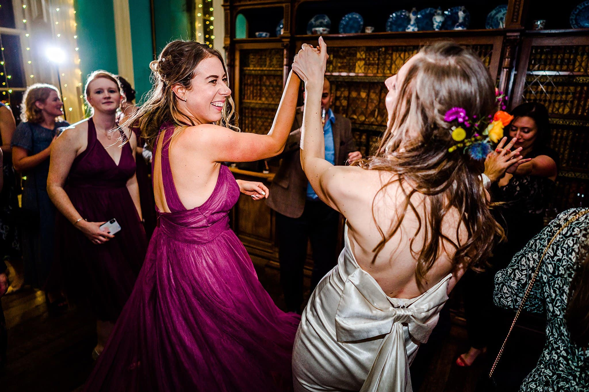 Bride dances with her bridesmaid on the dancefloor at Prestwold Hall