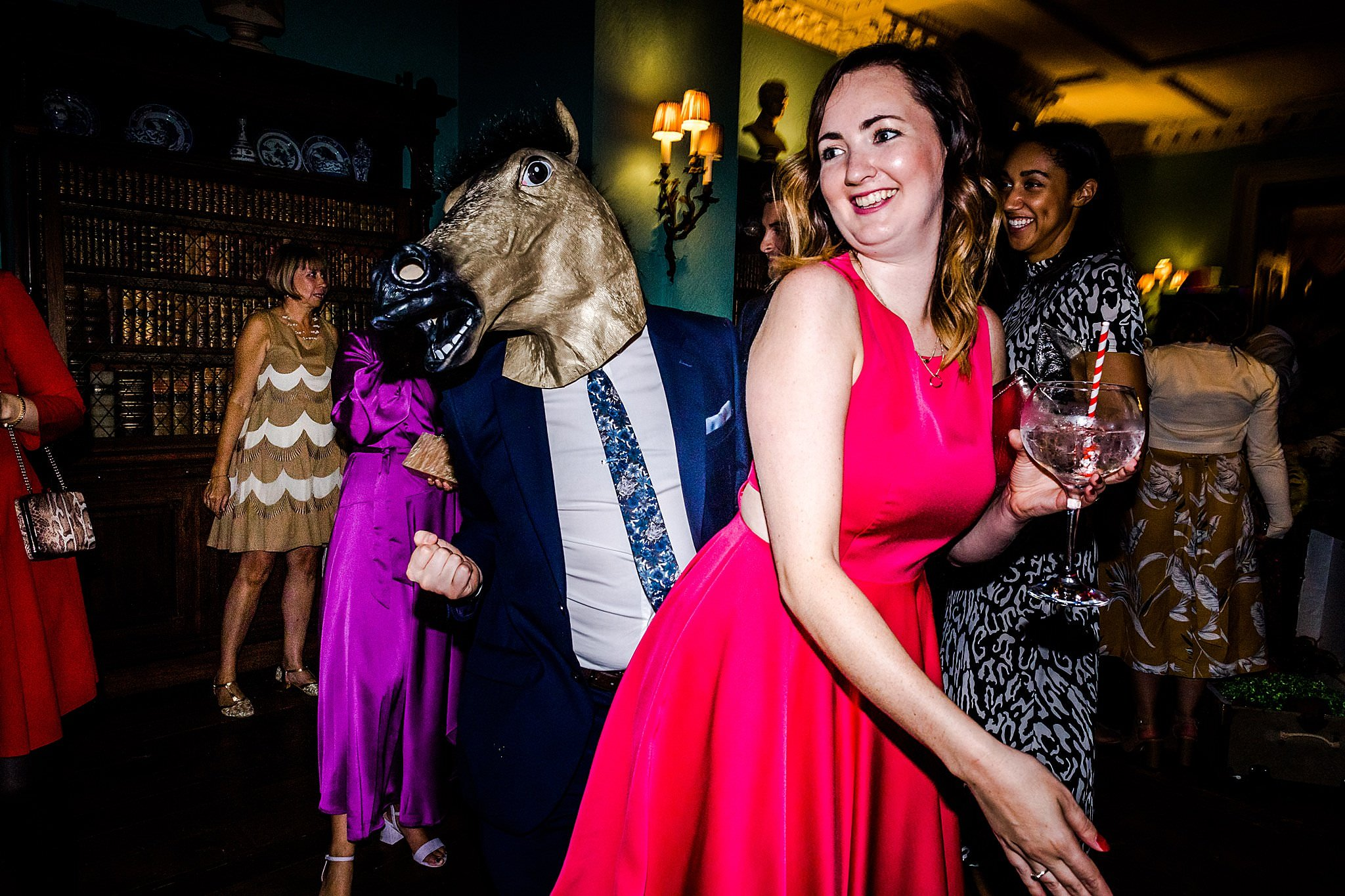 Wedding guest with a horse head mask on dances with another guest at a wedding at Prestwold Hall