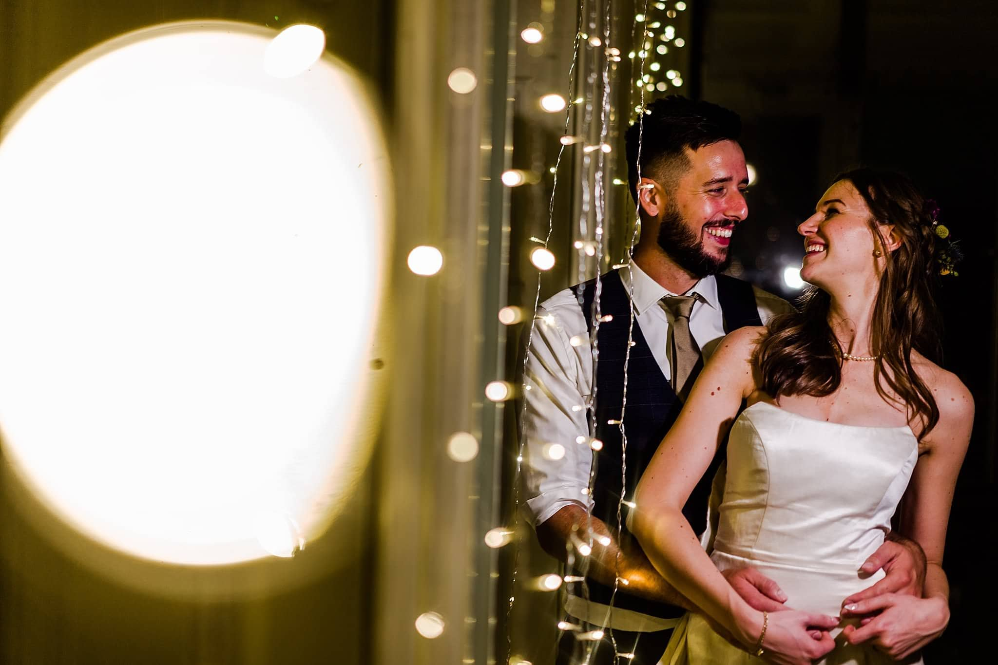 Bride and groom pose together in the string lights at Prestwold Hall
