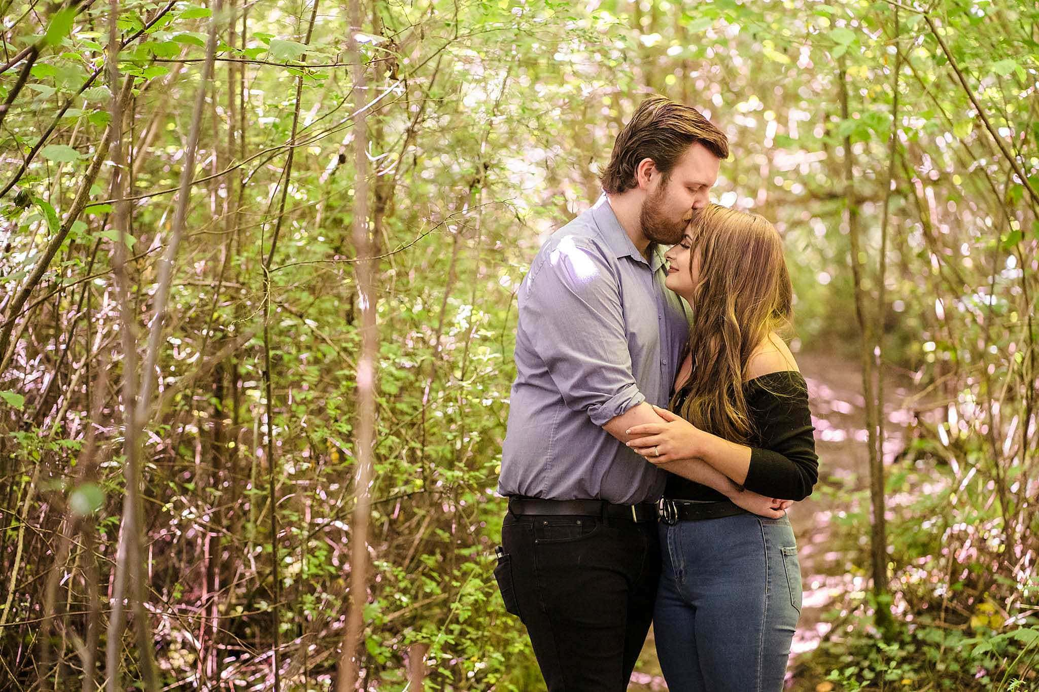 couple kiss surrounded by trees