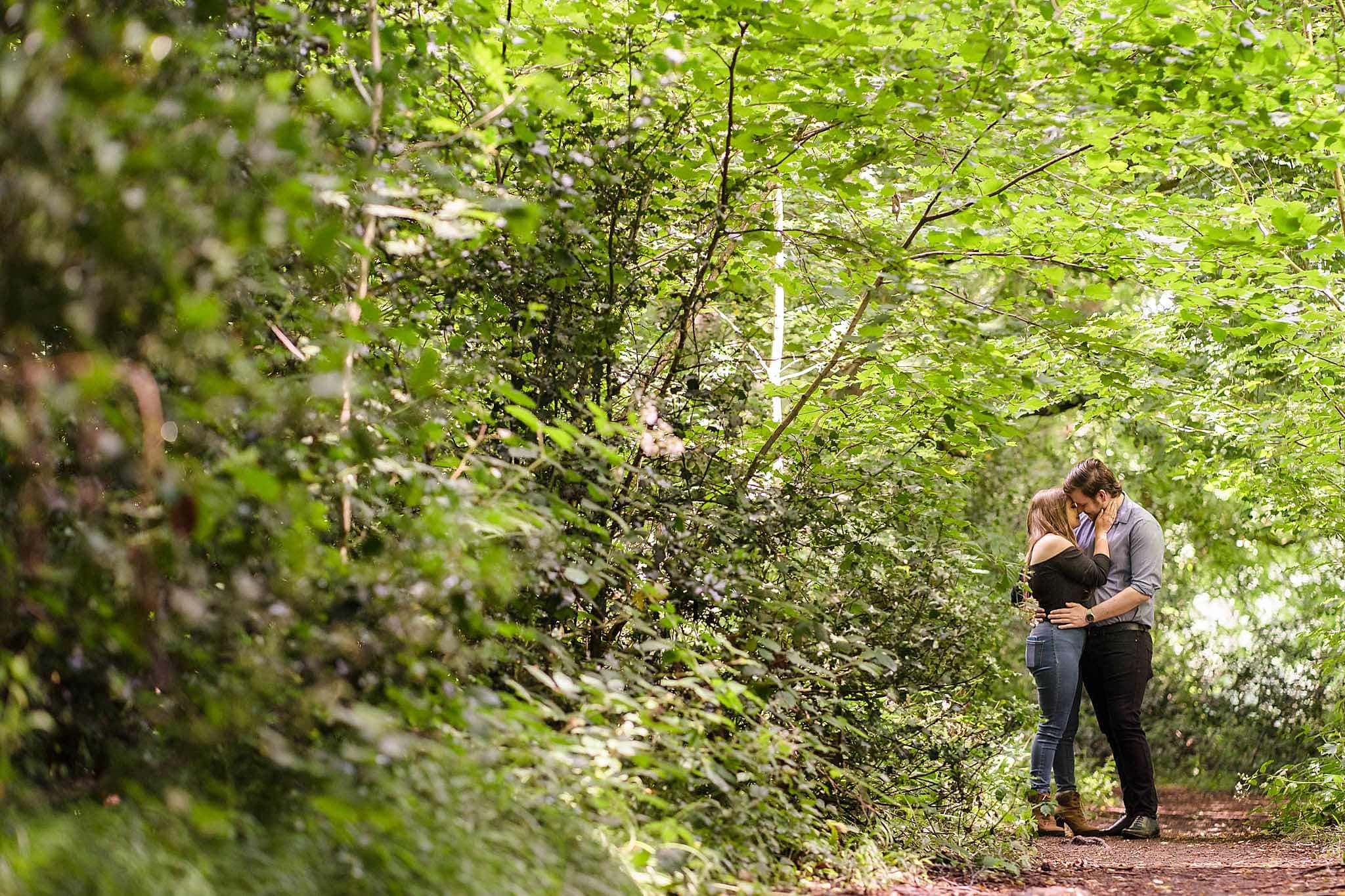 couple pose in tree line at swithland woods