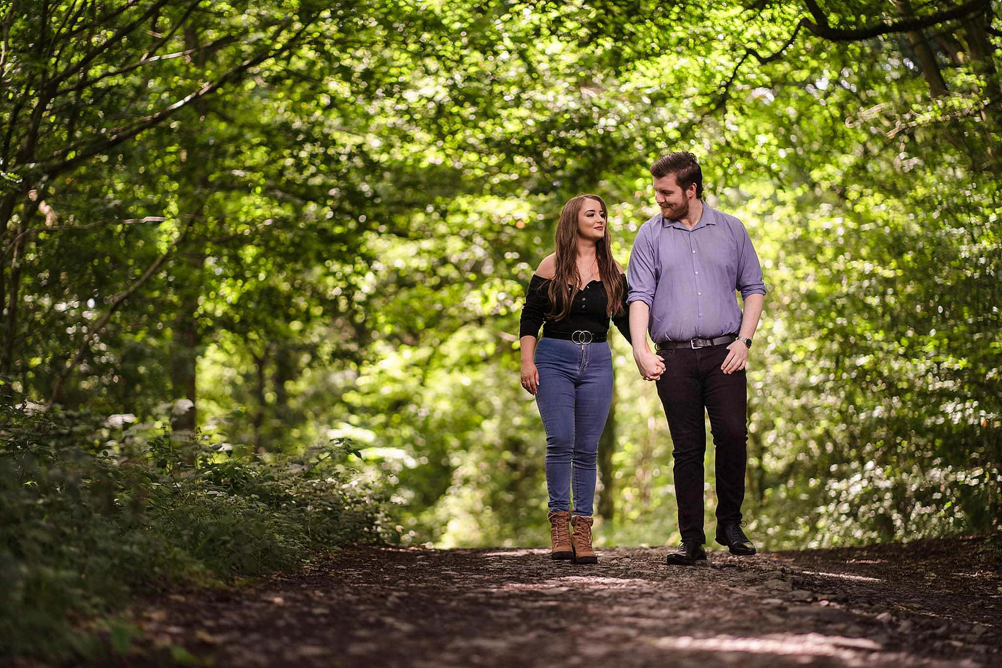 man and woman walk through swithland woods