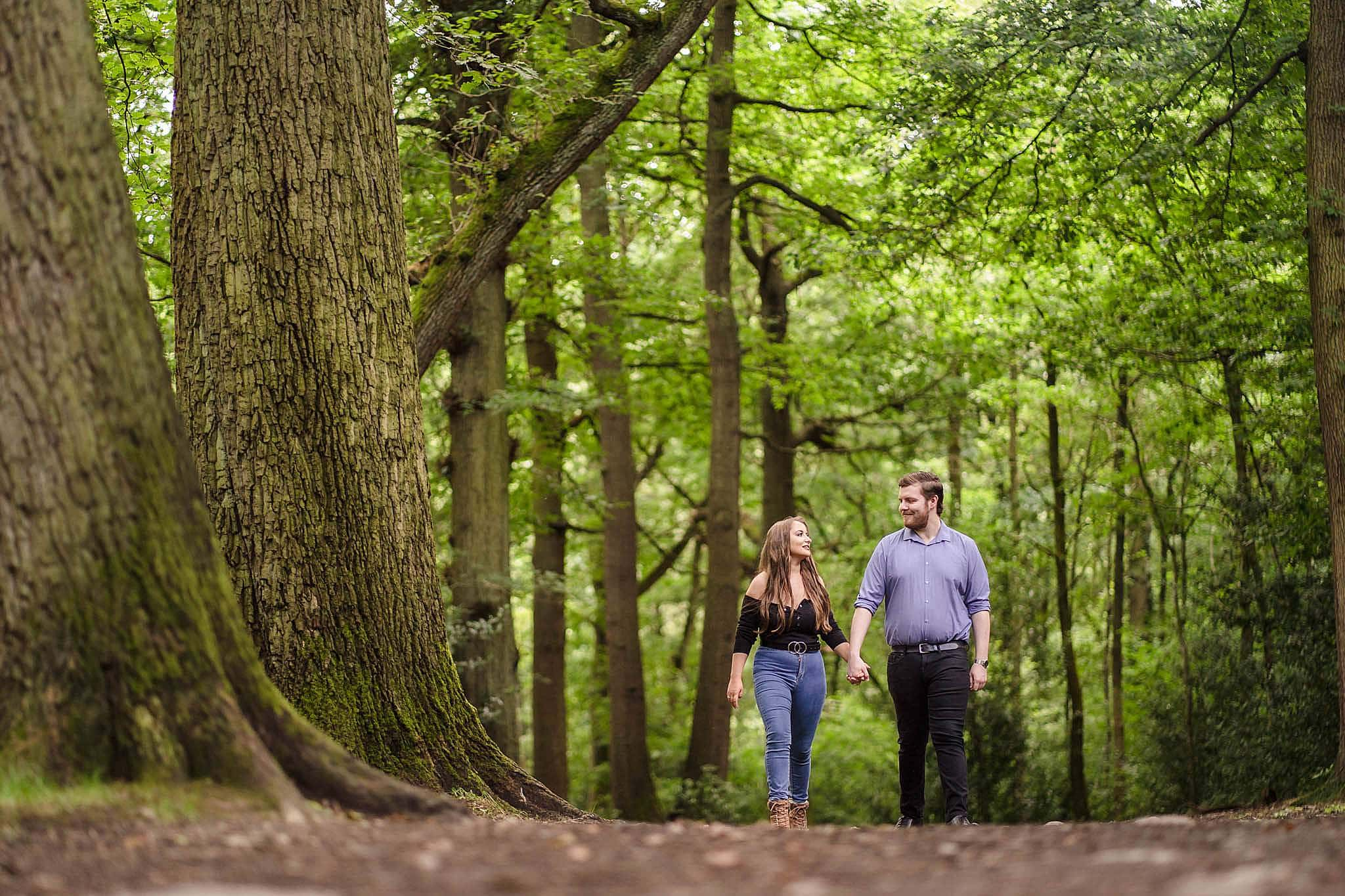Emma and Matt walk hand in hand through Swithland Wood