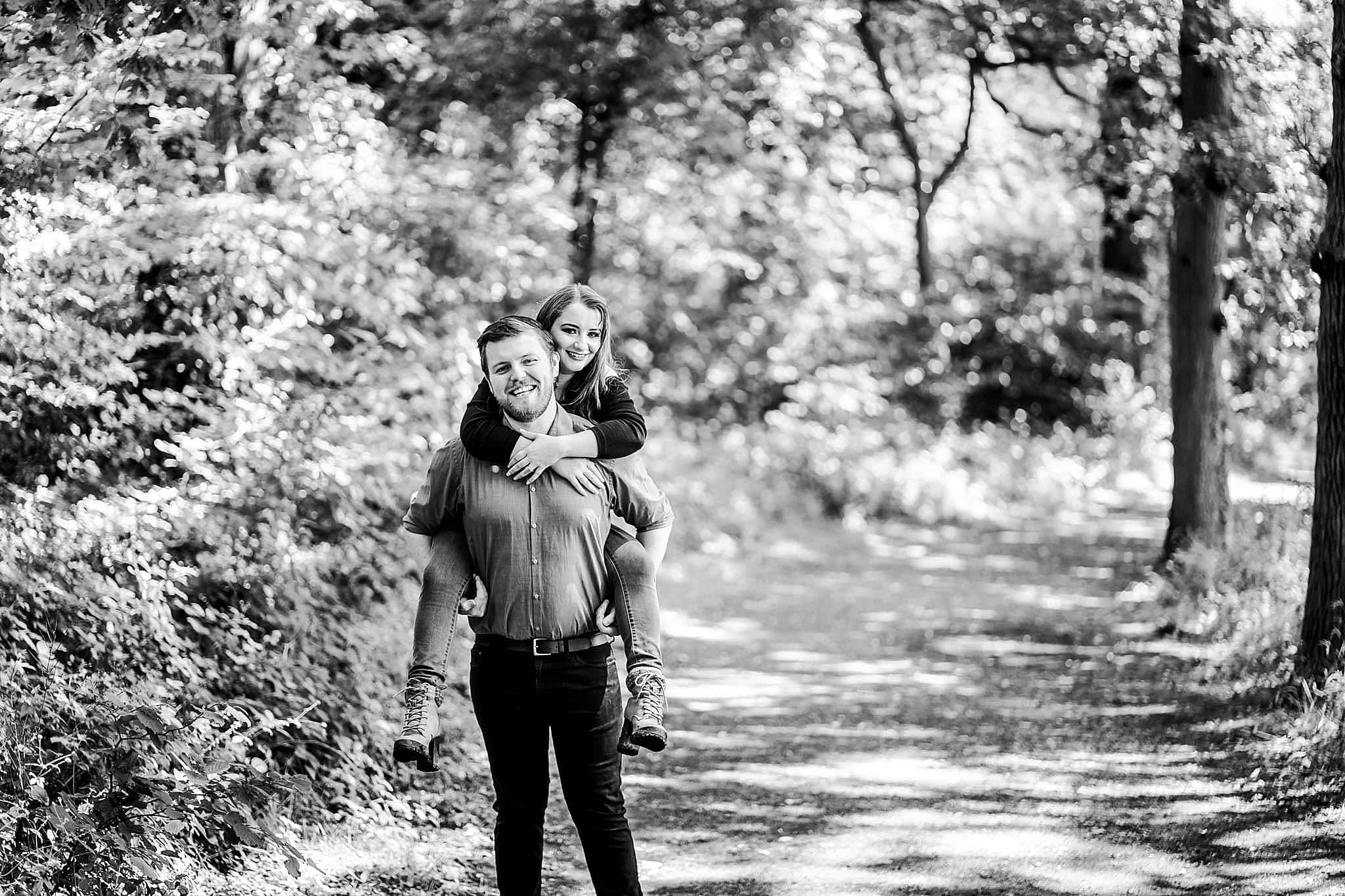 Black and white photo of man giving woman a piggyback through swithland woods